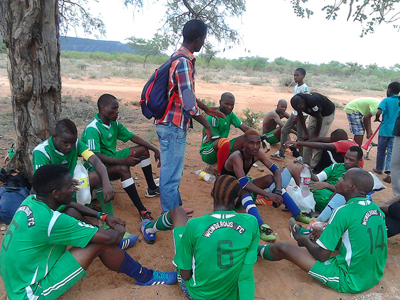 Volunteer mobilising a football team in Selebi-Phikwe for a discussion session on gender norms and Gender based Violence